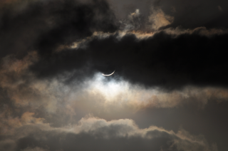 Clouds partially hide the solar eclipse. Courtesy of Romeo Durscher