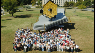 Members of the Webb team gather at NASA's Goddard Space Flight Center around a full-scale model of the space telescope.