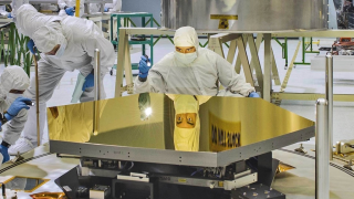 Engineers inspect one of the gold-plated beryllium mirror segments.