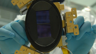 A Webb team member from the European Space Agency holds a single detector from the Near Infrared Spectrograph (NIRspec) instrument.