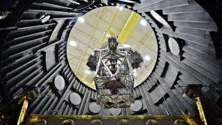 The OTE (Optical Telescope Element) Simulator, wrapped in a silver blanket, is here lowered into a vacuum chamber that simulated the cold of space.