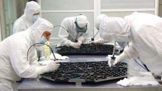 The Near Infrared Camera (NIRCam) team bonds the two halves of the NIRCam bench with epoxy.