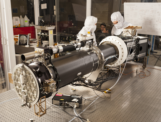 Photo of the instrument optics package prior to instrument level thermal vacuum testing.  The section to the left of the white collar is the 20cm solar telescope and the section to the right of the collar is the imaging spectrograph.  The spectrograph includes 18 optics used for transmitting the light from the telescope through the 4 channels to the focal planes as shown in the next sequence of images.  On top of the telescope assembly is the smaller guide telescope which provides the pointing signal to the secondary mirror of the telescope and to the attitude control system in the spacecraft.  The white collar is the primary mirror radiator used to reject the solar thermal load. Credit: LM Photo