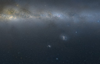 This visible light mosaic shows the LMC and SMC in context with the plane of our own galaxy, the Milky Way. Dusty filaments create dark traces across the bright central plane of the Milky Way, visible across the top of the image. Below it, separated by about 21 degrees, lie the LMC and SMC, the closest major galaxies to our own. Lying about 163,000 and 200,000 light-years away, respectively, the LMC and SMC orbit each other as well as our own Milky Way galaxy. The LMC is about one-tenth the size of the Milky Way and contains only 1 percent of its mass. The SMC is half the LMC's size and contains about two-thirds of its mass. Credit: Axel Mellinger, Central Michigan Univ.